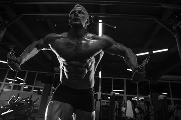 Fototapeta na wymiar Brutal strong bodybuilder man pumping up muscles and train gym