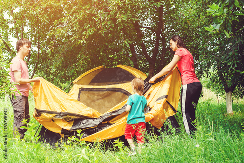 Fotografie, Obraz  Happy family putting up a tent together in woods. Toned.