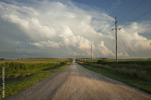 Fototapeta Rural road with dramatic clouds in southern Minnesota at sundown obraz