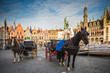 canvas print picture - Horse carriages on Grote Markt square in medieval city Brugge at morning, Belgium.