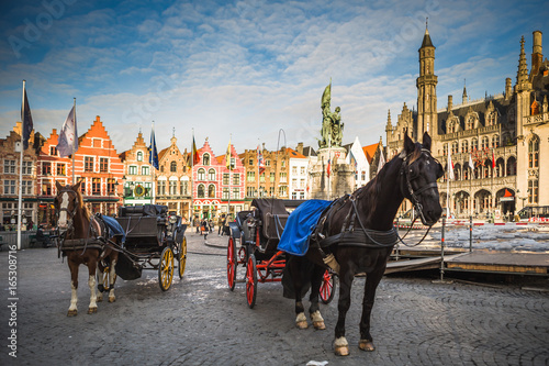 Horse carriages on Grote Markt square in medieval city Brugge at morning, Belgium.