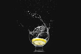 Fototapeta Łazienka - Splash in a glass of pure water with a lemon isolated on a black background