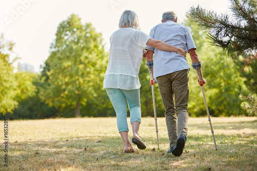 Canvas Print Caregiver helps man walking with crutches