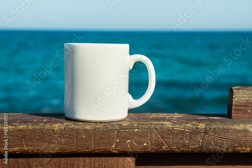 White mug, mock up, empty space for artwork, text, standing on wood plank, turquoise sea, clear blue sky, horizon, sunlight, nature