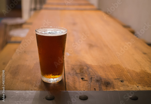 Photo  Glass of beer on wooden table in pub background