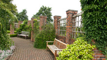 Benches In A Walled Garden With Monoblock Path And Red Brick Pillars