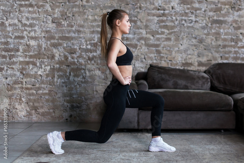 Photo Profile view of sporty girl doing lunges working-out leg muscles and glutes in l