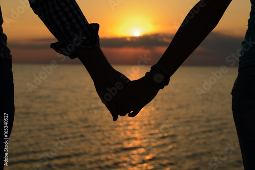 Fotografia  A loving couple (silhouettes of a man and a girl) hold hands in the rays of light at sunset on the sea on a pier