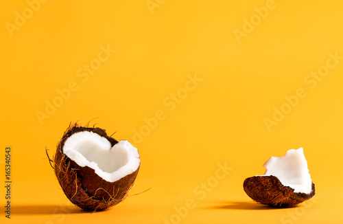 Fototapeta Fresh coconut on a bright yellow background