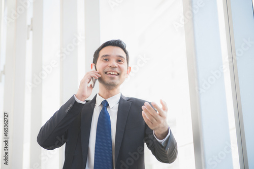 Fototapety, obrazy: Man on smart phone - young business man in airport. Casual urban professional businessman using smartphone smiling happy inside office building or airport. Handsome man wearing suit indoors.
