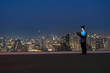 Asian technician engineer standing and using the laptop over the cityscape background at night time, Business success and technology concept