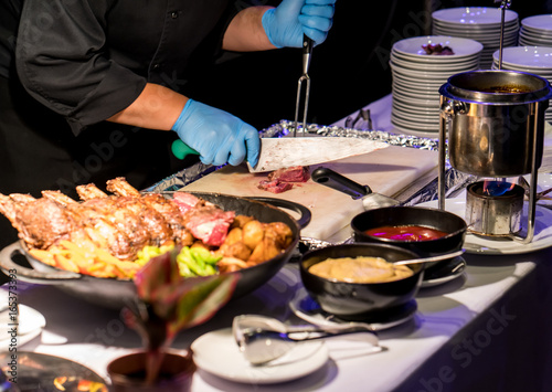 Valokuva  Hotel chef slicing grilled beef spare rib with long knife and fork