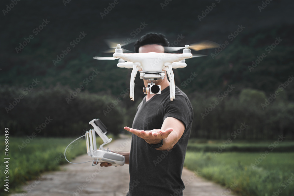 Fototapeta Drone is taking off from man hands. Young man releasing aerial copter to fly with small digital camera. Modern technology in our life.