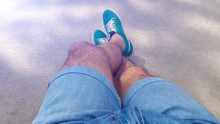 Man With Hairy Legs In Denim Shorts And Green Sneakers