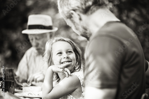 Fotografia  family lunching in the garden focus on a beautiful little girl