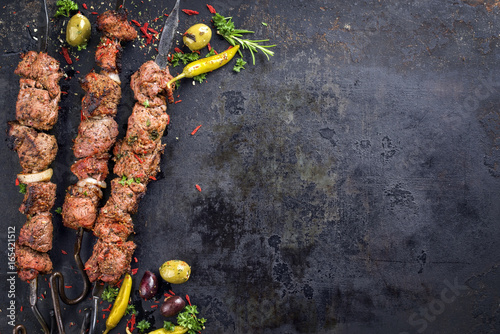 Traditional Russian shashlik on a barbecue skewer as top view with copy space on old rusty metal sheet