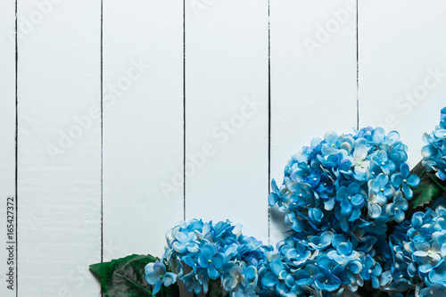 Montage in der Fensternische Hortensie Blue hydrangea flowers on a white wooden texture background.Artificial Flowers