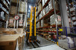 Yellow forklift truck waiting in aisle between rows of tall racks with packed goods in empty warehouse