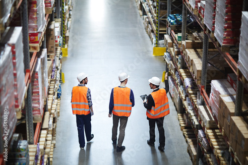 Group of warehouse workers wearing hardhats and reflective jackets waking in ais Canvas Print