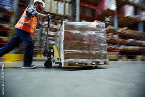 Blurred motion shot of warehouse worker wearing hardhat and reflective jacket pu Fototapeta