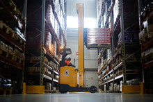 Side View  Portrait Of Warehouse Worker Using Reach Fork Truck To Load Pallet With Boxes On Tall Rack