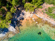 Aerial view of sandy beach with rocks and clear turquoise water