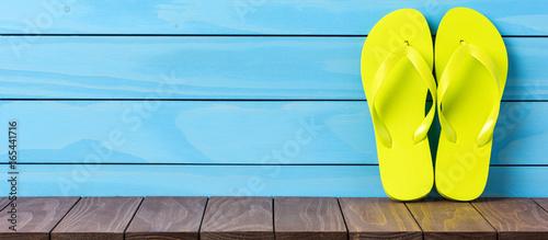 Green flip flops on wooden background. Close up