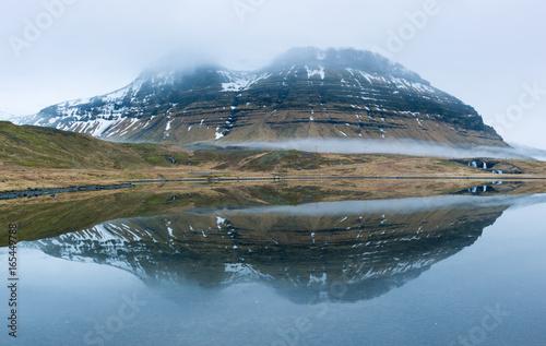 Foto auf Gartenposter Reflexion Montagne innevate fra le nuvole con riflesso sulla laguna, Islanda