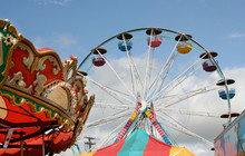 Fair Carnival Rides And Tent Top Against Blue Sky.