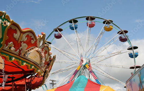 In de dag Amusementspark Fair carnival rides and tent top against blue sky.