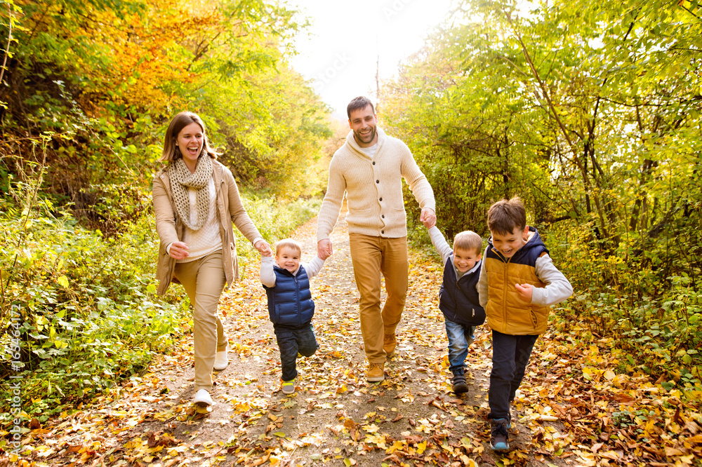 Fototapeta Beautiful young family on a walk in autumn forest.
