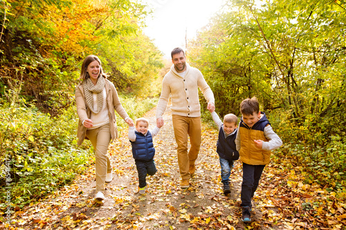 Fototapeta Beautiful young family on a walk in autumn forest. obraz