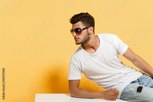 Fotografía  Good-looking young man in sunglasses wearing white t-shirt and jeans leaning upon white surface