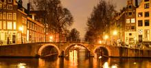 Amsterdam By Night. Illuminated Bridge Over Water Canal, Gracht. Netherlands