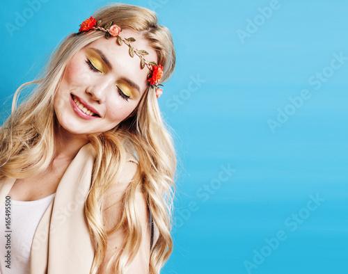 mloda-piekna-dziewczyna-z-blond-wlosami-i-wiankiem-na-glowie-na-turkusowym-tle