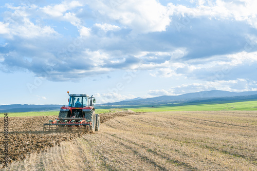 agricultural machinery in the foreground carrying out work in the field Obraz na płótnie