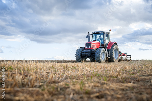 agricultural machinery in the foreground carrying out work in the field.