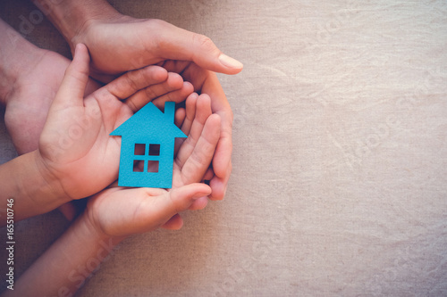 Fotografía  Adult and child hands holding paper house, family home and real estate concept