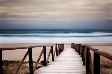 Panel Szklany Podświetlane Molo Paesaggio marino con passaggio dalla spiaggia al mare