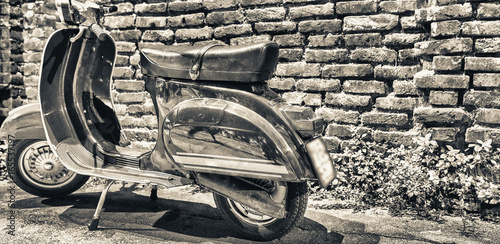 Foto op Canvas Scooter MILANO, ITALY - SEPTEMBER 25, 2015: Old Vespa parked along Navigli at night. Vespa is an old italian motorbike