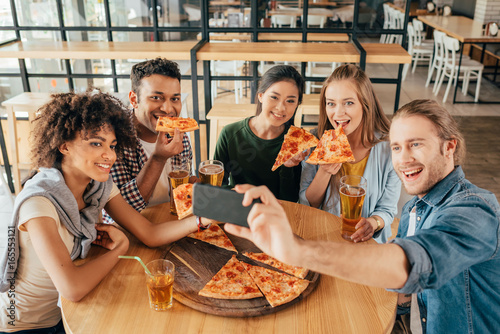 Poster Pizzeria Young man taking selfie with multiethnic friends having pizza in cafe