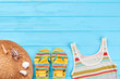 Female beach clothing on bottom border. Blue wooden surface and summer accessories.
