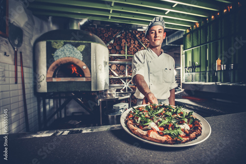 Poster Pizzeria Food concept. Preparing traditional italian pizza. Young smiling chef in white uniform and gray hat show ready dish with green rucola herbs in interior of modern restaurant kitchen. Ready to eat.