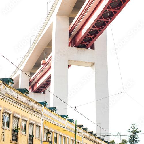 Obraz na plátne  LISBON, PORTUGAL - October 29, 2016: The 25 de Abril bridge over city buildings or residential quarter in Lisbon, Portugal