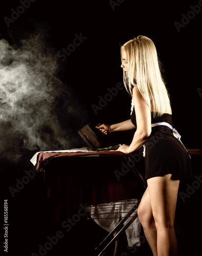 sexy blonde woman in housekeeper suit, ironing white shirt with old iron Billede på lærred