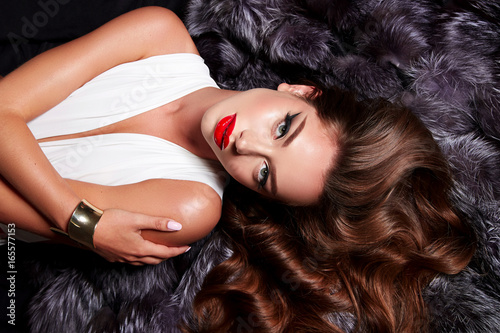 Fotografie, Obraz Beautiful young girl with a bright make-up in white body and long shiny wavy hair lies on a fur coat