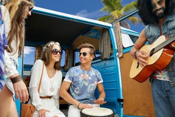 hippie friends playing music over minivan on beach