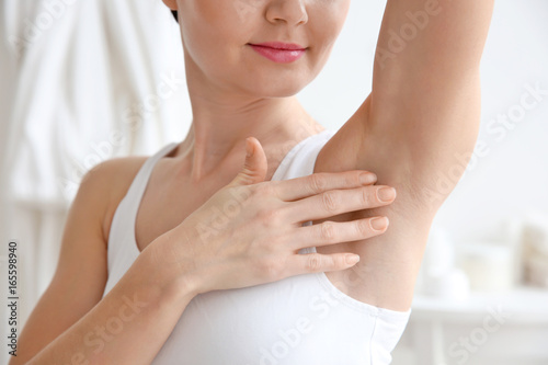 Closeup view of woman touching her armpit on blurred background Canvas Print