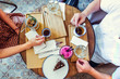 Couple of Man and woman on date having breakfast in the morning in cafe. Granola, chocolate cake, smoothie and hot coffee on the table. Flatlay, selective focus.