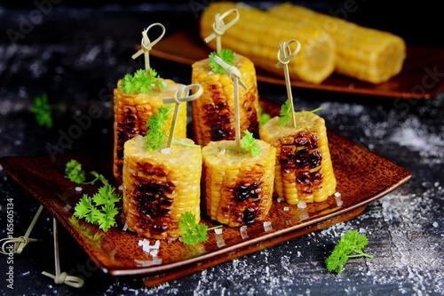 Plakat kukurydza z grilla z solą, natka pietruszki na szaszłykach